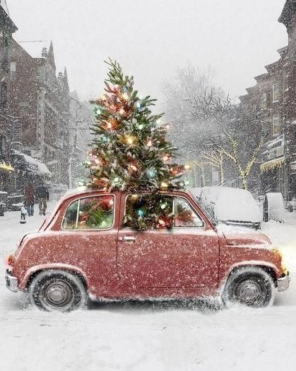 lit christmas tree in snow and vintage car
